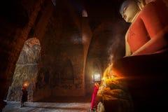 De monnik in de oude stad van Bagan bidt een standbeeld van Boedha met kaars stock fotografie