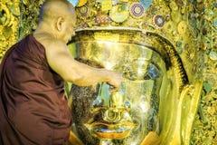 De monnik voert dagelijks ritueel van het wassen van het Gezicht van Maha Muni Sacred Living Image op de vroege ochtend in Mandal royalty-vrije stock afbeeldingen