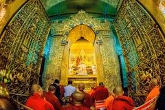 De monnik voert dagelijks ritueel van het wassen van het Gezicht van Maha Muni Sacred Living Image op de vroege ochtend in Mandal royalty-vrije stock afbeelding