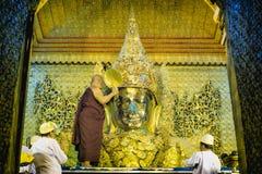 De monnik voert dagelijks ritueel van het wassen van het Gezicht van Maha Muni Sacred Living Image op de vroege ochtend in Mandal royalty-vrije stock foto