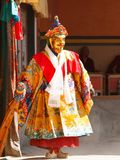 De monnik voert een godsdienstige gemaskeerde en gekostumeerde geheimzinnigheid dans van Tibetaans Boeddhisme bij het traditionel stock fotografie