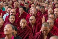 De monniken en tibetan mensen die aan zijn Heiligheid luisteren 14 Dalai die Lama Tenzin Gyatso het onderwijs in zijn woonplaats  Royalty-vrije Stock Afbeelding