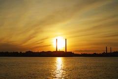 De montages van de zon achter machtspijpen Stock Foto