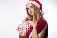 De mooie aantrekkelijke jonge blondevrouw in rode hoed ontving een gift voor het nieuwe jaar, houdt een doos op haar hand en slui royalty-vrije stock foto