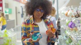 De mooie Afrikaanse Amerikaanse vrouw met een afrokapsel in de winkel kiest koppen stock video