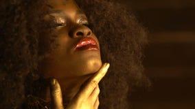 De mooie Afrikaanse vrouw met rode glanzende lippen, gouden bronsoogschaduw en krullend haar raakt teder haar gezicht en stock videobeelden