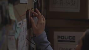 De mooie agent die van de wetshandhaving de identiteit van terrorist aan het licht brengen, de defensie van de staat stock video