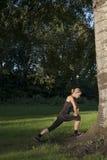 De mooie atletische jonge volwassen vrouw doet in openlucht oefeningen in park stock afbeeldingen