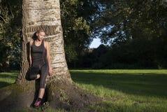 De mooie atletische jonge volwassen vrouw neemt een onderbreking tijdens het openlucht uitoefenen stock foto