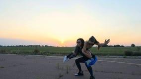 De mooie, atletische, jonge vrouw in zonnebril, in legging, voert hurkzit uit, die een meisje in haar wapens, oefeningen binnen h stock video