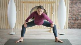 De mooie atletische sportieve vrouw die yoga doen oefent binnen uit Uitrekkende praktijk in de gymnastiek stock video