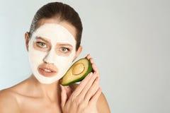 De mooie avocado van de vrouwenholding dichtbij haar gezicht met kleimasker tegen grijze achtergrond royalty-vrije stock afbeeldingen
