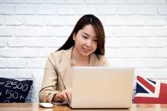 De mooie Aziatische bedrijfsvrouwen werken met laptop in koffie Stock Foto's