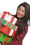 De mooie Aziatische vrouw draagt de giften van Kerstmis stock afbeeldingen