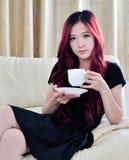 De mooie Aziatische vrouwen met rood snakken haar het drinken koffie Stock Foto