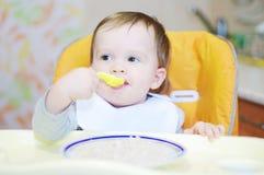 De mooie baby eet graangewas Stock Afbeeldingen