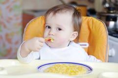 De mooie baby eet rijst-melk met pompoen Stock Foto's