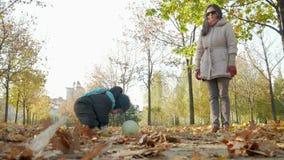 De mooie baby speelt in de herfstpark met haar moeder over gevallen bladeren Een kind speelt met een witte voetbalbal stock footage
