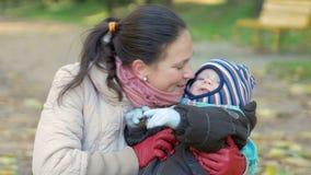 De mooie baby speelt in de herfstpark met haar moeder over gevallen bladeren Het kind is warm gekleed in een kostuum en stock videobeelden