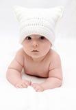 De zuigeling in witte hoed ligt op bed Royalty-vrije Stock Fotografie