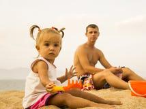 De mooie baby zit het onder ogen zien van de camera en het spelen met stuk speelgoed hark in het zand op het strand stock afbeeldingen
