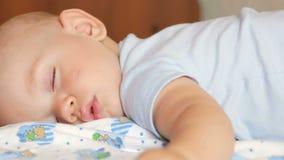 De mooie babyslaap in grappig stelt op een bed Onder de babyluier, de jongen over een jaar stock video