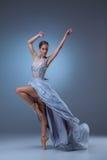 De mooie ballerina die in blauwe lange kleding dansen Stock Afbeelding