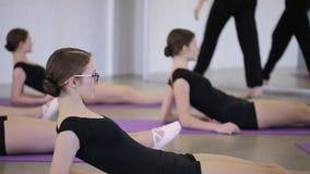 De mooie ballerina's verwarmt hun spieren alvorens in klaslokaal op te leiden stock video