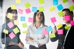 De mooie bedrijfsmensen gebruiken stickers en teller, bespreken ideeën en glimlachen tijdens de conferentie in bureau Het werk va stock afbeelding