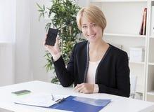 De mooie bedrijfsvrouw in het bureau toont smartphone scre Royalty-vrije Stock Afbeeldingen