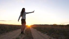 De mooie bedrijfsvrouw reist en neemt een selfiefoto gebruikend een mobiele smartphone op de weg tegen de zonsondergang stock video