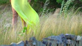 De mooie benen die van jong meisje lange gele kleding dragen die blootvoets zand op overzees strand lopen dicht winden omhoog win stock videobeelden