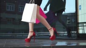 De mooie benen in schoenen met hielen gaan langs het venster van de glaswinkel Sexy benenclose-up Langzame Motie stock video