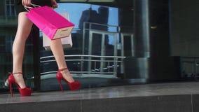 De mooie benen in schoenen met hielen gaan langs het venster van de glaswinkel Sexy benenclose-up Mooi jong meisje in rode kledin stock video