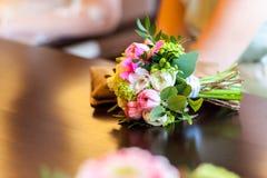 De mooie bezinning van het bloemboeket over houten lijst stock afbeelding