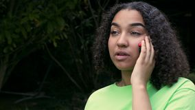 De mooie biracial Afrikaanse Amerikaanse jonge vrouw die van de meisjestiener op een telefoongesprek op haar mobiele celtelefoon  stock videobeelden