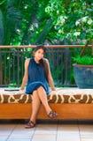 De mooie biracial zitting van het tienermeisje op beschermde bank in openlucht Royalty-vrije Stock Fotografie
