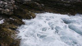 De mooie blauwe overzeese golven verpletteren tegen de rotsen en de klippen op zonnige dag in Budva, Montenegro Golven met schuim stock videobeelden