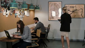 De mooie blonde bedrijfsvrouw gebruikt tablet dan gaat in modern startbureauteam in werkplaats Langzame mo, steadicam schot stock video