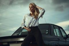 De mooie blonde dame in zwarte gestreepte hoogte waisted broek en overmaatse witte blouse die zich bij haar oude auto bevinden we royalty-vrije stock afbeelding