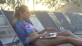 De mooie blonde glimlachende vrouw in bikini en het jeansoverhemd die aan een laptop computer werken terwijl het zitten sunbed op stock video