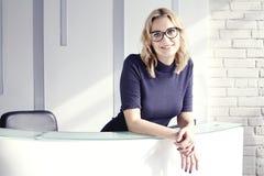 De mooie blonde vriendschappelijke vrouw achter het ontvangstbureau, komt en glimlachend samen Zonneschijn in modern bureau stock afbeelding