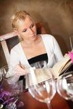 De mooie blonde vrouw kijkt op menu in restaurant. stock afbeeldingen