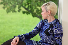 De mooie blonde vrouw kijkt uit venster royalty-vrije stock fotografie
