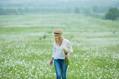 De mooie blonde vrouw van de meisjesdame op groen gebied die met bloemenkamille het witte overhemd van de jeanshoed dragen onder  Royalty-vrije Stock Afbeeldingen
