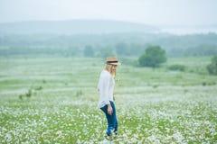 De mooie blonde vrouw van de meisjesdame op groen gebied die met bloemenkamille het witte overhemd van de jeanshoed dragen onder  Stock Afbeelding