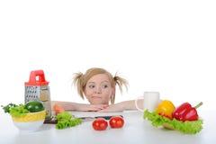 De mooie blonde zoekt verse groenten. Stock Foto