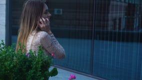 De mooie blondedame zit in de straat en spreekt mobiele telefoon stock footage