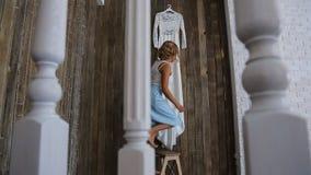 De mooie blondevrouw beklimt op kleine trapladder om haar huwelijkskleding te nemen stock videobeelden