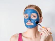 De mooie blondevrouw die blauw klei gezichtsmasker hebben is door schoonheidsspecialist van toepassing royalty-vrije stock foto's